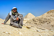 Camel guide sitting on the Sand dunes next to Pyramid of Unas with Step Pyramid in the background