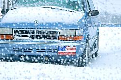 blue van truck american flag bumper sticker white snow blizzard storm winter auto van in parking lot cold winter blizzard concept CONCEPT STOCK PHOTOS CONCEPT STOCK PHOTOS