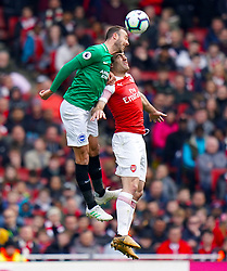 Arsenal's Sokratis Papastathopoulos (right) and Brighton & Hove Albion's Glenn Murray battle for the ball during the Premier League match at the Emirates Stadium, London.
