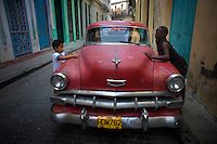 vintage chevy in cuban streets with children