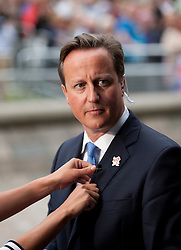 © Licensed to London News Pictures. 10/09/2012. LONDON, UK. British Prime Minister David Cameron has a microphone fitted for an interview outside a reception for Olympic and Paralymic athletes at the Queen Elizabeth II Conference Centre in London today (10/09/12). Photo credit: Matt Cetti-Roberts/LNP