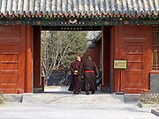 two monks walking through the entrance towards there temple China Beijing