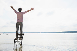 Young man standing chair lake alone sunset