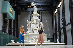 "© Licensed to London News Pictures. 24/07/2020. LONDON, UK. Tate staff wearing facemasks pose next to ""Fons Americanus"", 2019, by Kara Walker. Press preview ahead of the reopening of Tate Modern on 27 July after the easing of coronavirus pandemic lockdown restrictions by the UK government.  Visitors will need to book timed tickets online and follow one-way routes around the gallery space along with observing social distancing rules.  Photo credit: Stephen Chung/LNP"