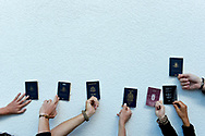 Travelers hold their passports up against a wall, representing the countries of Australia, the United States, Canada, Denmark, and New Zealand