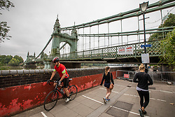 © Licensed to London News Pictures. 14/08/2020. London, UK. Cyclists and walkers go around Hammersmith Bridge which crosses the River Thames in West London after Fulham Council suddenly closed it to all traffic Thursday night due to safety concerns. Hammersmith Bridge has been close to all traffic including pedestrians, cyclists and boats going under it after cracks in the bridge have become larger by the heatwave. Photo credit: Alex Lentati/LNP
