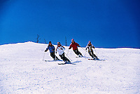 Four women skiing together in synchronization, Winter Park Resort, Colorado USA