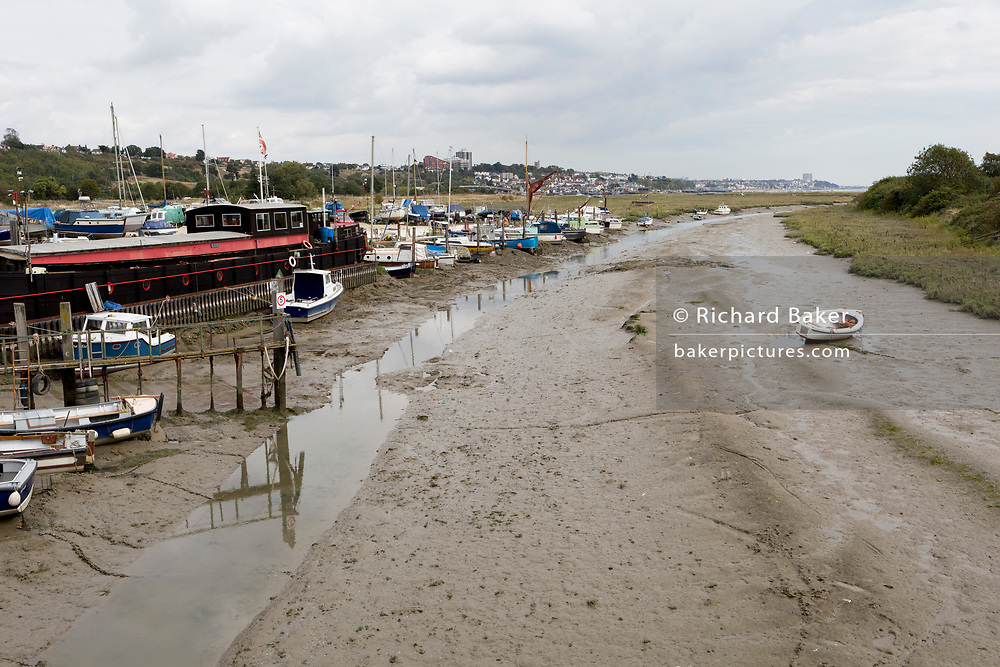 A landscape of assorted boats and estuary vessels at low-tide at Leigh creek in Old Leigh, on 10th September 2019, in Leigh-on-Sea, Essex, England. The land to the right is Two tree Island, a marshland nature reservebetween Leigh and Canvey Island.