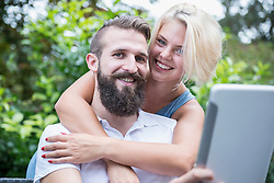 Young man using digital tablet with his girlfriend embracing from behind in garden, Bavaria, Germany