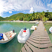 Boats on a jettty near Foxys Bar on Jost Van Dyke in the British Virgin Islands in the Caribbean. United Kingdom. High resolution panorama.