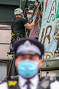 "Protestor Removal Unit of the police is seen removing the glued hand of a father and ex-teacher who climbed onto the canopy above the front door of the Department for Business and Energy building where he spray-painted '4 degrees = Mass murder' and unfurled a banner reading 'Act Now For All Our Children' on Monday, Sept 7, 2020. He said: ""My youngest child is only one. Within her lifetime scientists tell us that we are likely to see 4 degrees of global warming he continued. <br /> Environmental nonviolent activists group Extinction Rebellion enters its 7th day of continuous ten days protests to disrupt political institutions throughout peaceful actions swarming central London into a standoff, demanding that central government obeys and delivers Climate Emergency bill. (VXP Photo/ Vudi Xhymshiti)"