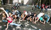 Studenten wringen zich op het Domplein in Utrecht in allerlei bochten voor een opdracht tijdens de introductieweek. Vandaag zijn in Utrecht de introductiedagen, onder de noemer UIT, van start gegaan. Eerstejaars studenten maken onder begeleiding van ouderejaars kennis met elkaar en de stad waar ze gaan studeren.<br /> <br /> New students of the University of Utrecht are posing for a photo in the center of the town during their introduction.