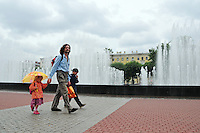 A proud father walks with his children near the beautiful fountains at Ploshad Lenina railroad station in St. Petersburg, Russia.
