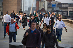 © Licensed to London News Pictures.  27/08/2021. London, UK. Commuters cross London Bridge this morning. The government have estimated that over 100,000 lives have been saved in England by the vaccination rollout.Photo credit: Marcin Nowak/LNP
