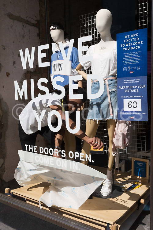 As the UKs Coronavirus lockdown continues to ease, retailers re-open their doors to shoppers, an employee of a Levis shop on Regent Street, unpeels the sticky stencil lettering telling customers that their business has been missed, on 18th June 2020, in London, England.