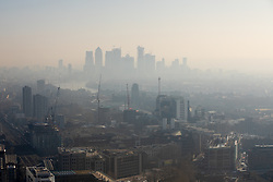 © Licensed to London News Pictures. 27/02/2019. London, UK. Smog is seen over the skyline of Canary Wharf in London this morning, following days of unseasonably warm weather in the capital. Temperatures on Tuesday 26 February reached 20.8C in Porthmadog, north-west Wales, which was the warmest winter day on record. Photo credit : Tom Nicholson/LNP