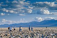 Tourists walking on salt encrusted rocks at Devlis, Golf Course, Death Valley National Park, California