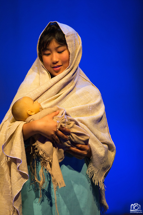 Emily Than acts as Mary holding baby Jesus during a story of Easter before the Easter Egg Hunt at Christ Community Church in Milpitas, California, on March 30, 2013. (Stan Olszewski/SOSKIphoto)