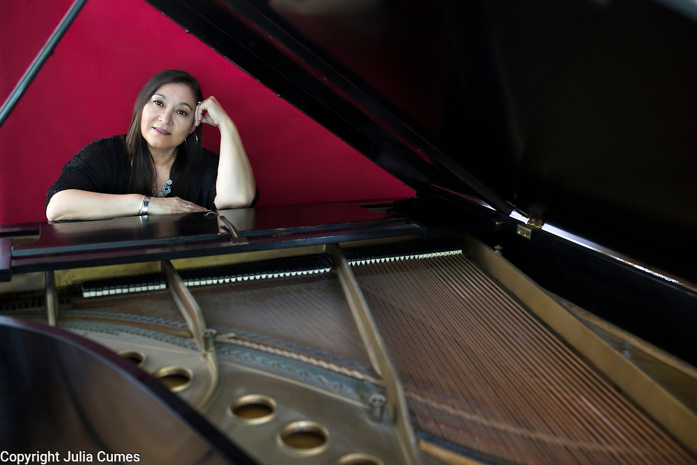 """Singer/song-writer, Kim Moberg, 58, is framed by the 102 year-old Steinway grand piano in her home in Centerville, MA. When Kim and her husband were trying to have a second child years ago, she discovered a lump. She was put on tamoxifen and had a lumpectomy and thought everything was fine. """"Soon after that my mom was diagnosed with breast cancer and died shortly after at the age of 63; then my younger sister was diagnosed at 41 and died after a long struggle with it,"""" she explains. Kim got genetically tested and discovered the had the BRCA2 genetic mutation. Since it put her at extremely high risk of developing cancer, she knew she had to have a double mastectomy and ovary removal. """"My husband, Rob is my rock and he did everything during that time period after the surgeries so I could concentrate on getting better,"""" she says. Kim, who was born in Alaska and whose mother is Native America (Tlingit), grew up surrounded by music. """"My mother was a classical pianist and taught me guitar when I was around 13 years-old,"""" she recalls. """"I'm drawn to musical stories that tug at feelings of melancholy, heartbreak and healing,"""" says Kim whose two daughters too have embraced music. While her younger daughter, Rebecca, is adopted, she knows her older daughter, Rachel, will too have to be genetically tested and potentially make decisions about risk factor health choices when she gets older."""