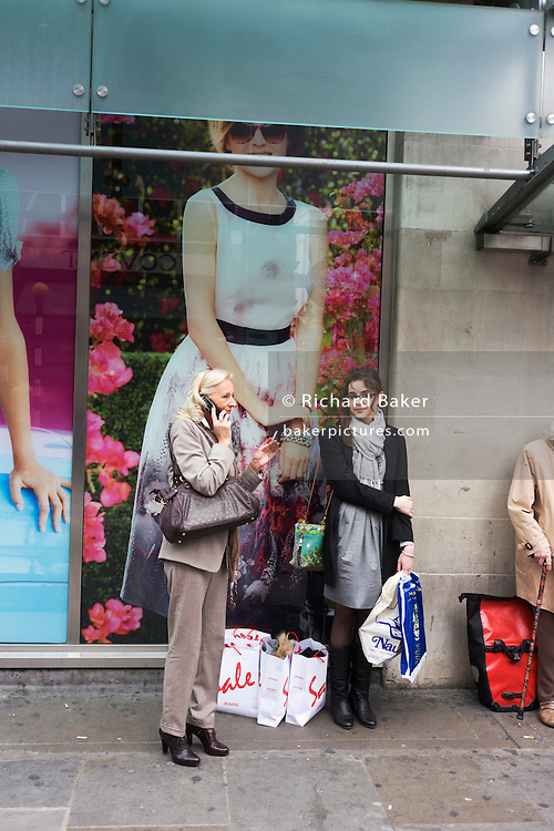 Women shopaholics rest during shopping expedition outside a branch of Marks & Spencer in central London.
