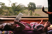A baby girl leisurely drains her bottle in a compartment with her mother.<br /> Inside the Dibrugarh-Kanyakumari Vivek Express, the longest train route in the Indian Subcontinent. It joins Kanyakumari, Tamil Nadu, which is the southernmost tip of mainland India to Dibrugarh in Assam province, near the border with Burma.