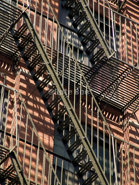 view of fire escapes with parallel shadows seen from below