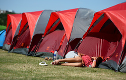 A man snoozes in the queue on day two of the Wimbledon Championships at the All England Lawn Tennis and Croquet Club, Wimbledon.