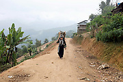 An Akha Nuquie woman carries firewood home along the new road to the remote village of Ban Chakhampa, Phongsaly province, Lao PDR. Whilst not affected directly by the Nam Ou Cascade Hydropower Dam 6 construction project, the village of Ban Chakhampa has benefitted from the new road passing by on the way to Ban Watai, a village which has recently been relocated due to the dam construction.