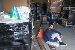 """© Licensed to London News Pictures. 07/05/2020. Salford, UK. Manager at Puro Medico SALAIMAAN MAJID (28) sits in the empty space in the warehouse from where the PPE was stacked up when it was stolen . £166,000 (one hundred and sixty six thousand pounds) worth of protective masks , which were destined for the NHS and care homes , have been stolen from a warehouse overnight (6th-7th May 2020) in what Greater Manchester Police are describing as a """" targeted burglary """" . Thieves cut the shutters at the loading bay of Puro Medico - which specialises in importing PPE such as masks from China and hand sanitiser from Poland - and stole several pallets of stock , which was loaded on to vans over a two hour period . Photo credit: Joel Goodman/LNP"""