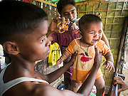 07 NOVEMBER 2014 - SITTWE, RAKHINE, MYANMAR: A Rohingya Muslim boy gets a haircut in an IDP camp for the Rohingya near Sittwe. After sectarian violence devastated Rohingya communities and left hundreds of Rohingya dead in 2012, the government of Myanmar forced more than 140,000 Rohingya Muslims who used to live in and around Sittwe, Myanmar, into squalid Internal Displaced Persons camps. The government says the Rohingya are not Burmese citizens, that they are illegal immigrants from Bangladesh. The Bangladesh government says the Rohingya are Burmese and the Rohingya insist that they have lived in Burma for generations. The camps are about 20 minutes from Sittwe but the Rohingya who live in the camps are not allowed to leave without government permission. They are not allowed to work outside the camps, they are not allowed to go to Sittwe to use the hospital, go to school or do business. The camps have no electricity. Water is delivered through community wells. There are small schools funded by NOGs in the camps and a few private clinics but medical care is costly and not reliable.   PHOTO BY JACK KURTZ