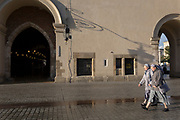 Two nuns walk beneath early morning architecture of the Cloth Hall on Rynek Glowny market square, on 23rd September 2019, in Krakow, Malopolska, Poland.