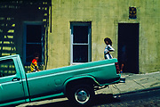 Children in the back of a pick-up truck in front of a green building in the Bronx