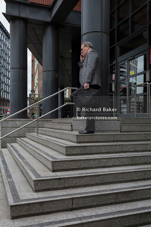 A businessman makes a call on his mobile phone at the top of steps outside a building housing tech businesses on Old Street roundabout aka Silicon Roundabout, 7th March 2018, in London England.
