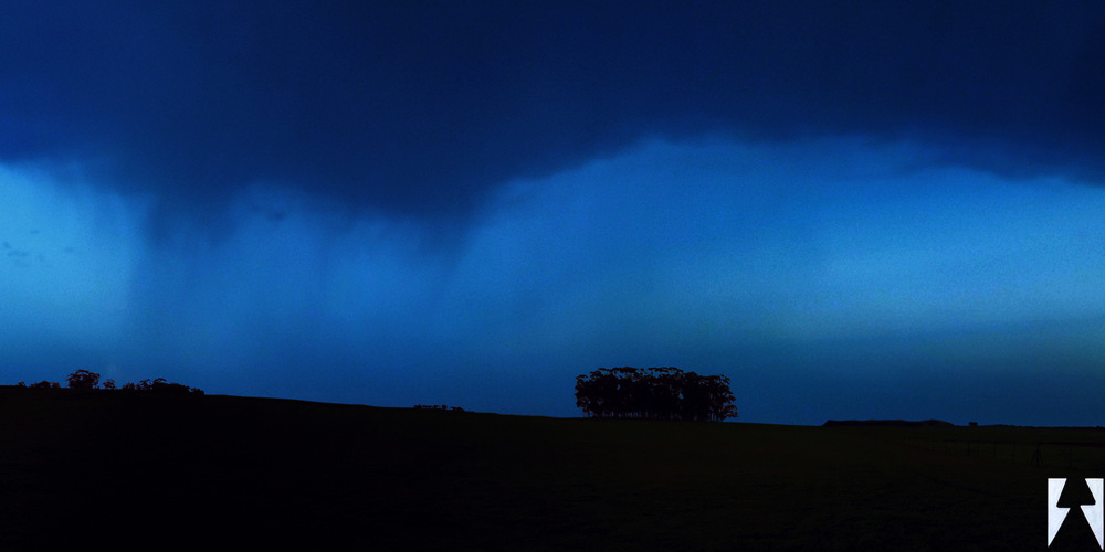 Panorama of a field swept by blue hues of rain as seen from afar.