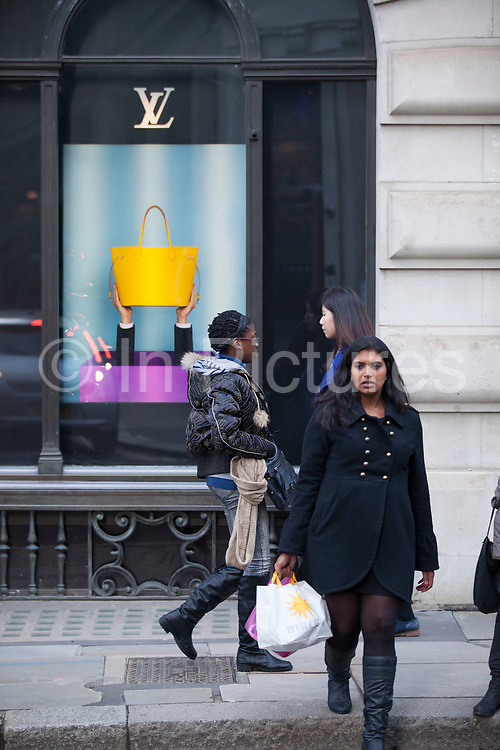 People walking past the shop window of Louis Vuitton store in the City of London, UK. Louis Vuitton Malletier, commonly referred to as Louis Vuitton or shortened to LV, is a French fashion house founded in 1854 by Louis Vuitton. The label's LV monogram appears on most of its products, ranging from luxury trunks and leather goods to ready-to-wear, shoes, watches, jewelry, accessories, sunglasses, and books.