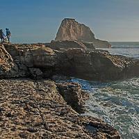 Hikers walk on oceanside rocks by Panther Beach, north of Santa Cruz, California