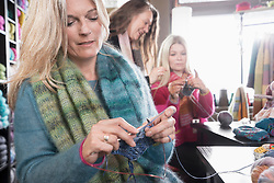 Mature woman knitting muffler in coffee shop, Bavaria, Germany