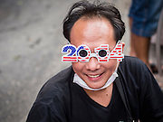 31 DECEMBER 2013 - BANGKOK, THAILAND: A man sells 2014 sunglasses on New Year's Eve in Bangkok. Hundreds of thousands of people pack into the Ratchaprasong Intersection in Bangkok for the city's annual New Year's Eve countdown. Many Thais go the Erawan Shrine and Wat Pathum Wanaram near the intersection to pray and make merit.     PHOTO BY JACK KURTZ