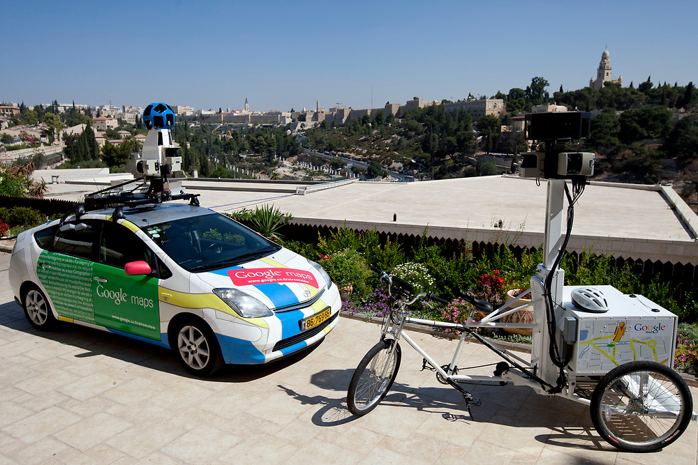 """A Google employee displays a Street View tricycle, following a press conference in Jerusalem, Israel, on September 12, 2011, in which Google has announced it will begin collecting images in Israel for the """"Street View"""" feature in Google Maps. In the coming weeks, Israel will join more than 30 other countries around the world which operate Street View, as Google cars and tricycles will begin driving and taking 360-degree photographs of streets, tourist destinations and other locations around the country. Images collected by the cameras mounted on vehicles will be processed and carefully stitched together to allow users to explore virtually and navigate cities, neighborhoods, streets and sites through panoramic street-level images."""