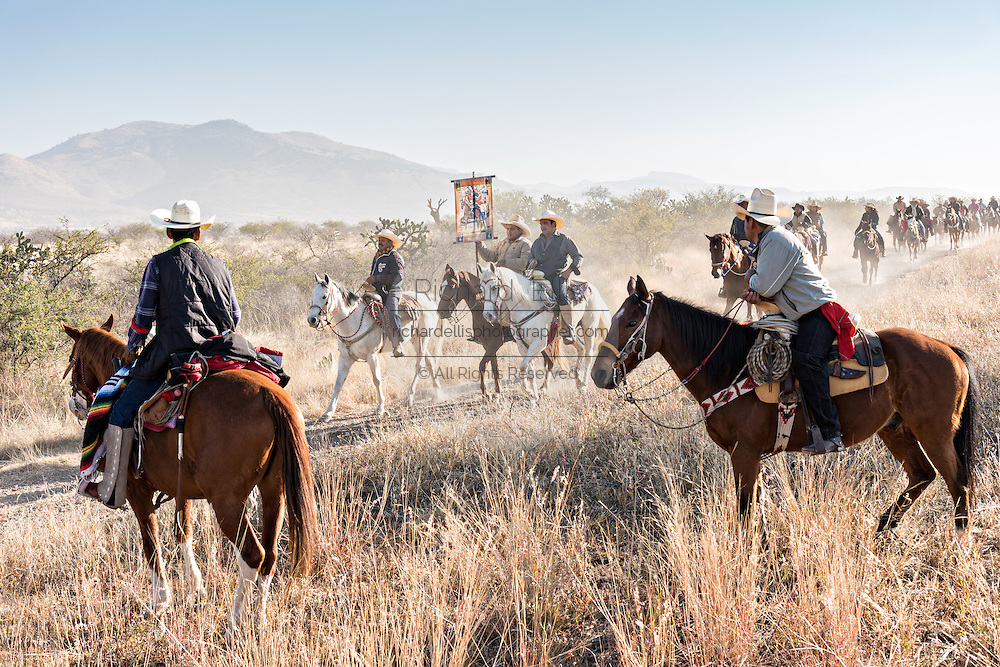 Volunteers watch as hundreds of Mexican cowboys ride past during the annual Cabalgata de Cristo Rey pilgrimage January 5, 2017 in La Trinidad, Guanajuato, Mexico. Thousands of Mexican cowboys and horse take part in the three-day ride to the mountaintop shrine of Cristo Rey stopping along the way at shrines and churches.