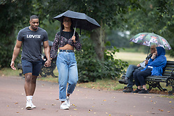 © Licensed to London News Pictures. 19/09/2021. London, UK. Members of the public shelter under umbrellas during a rain shower in Greenwich Park in South East London. A yellow weather warning for rain is in place for parts of England.  Photo credit: George Cracknell Wright/LNP