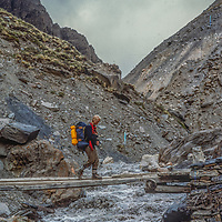 Meredith Wiltsie crosses a monsoon swollen stream while descending 17,769-foot Thorang La pass north of Annapurna in Nepal.
