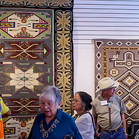 Gallery patrons browse an exhibit of award-winning pieces from the Gallup Intertribal Indian Ceremonial during a show at Art123 Gallery in downtown Gallup Tuesday.