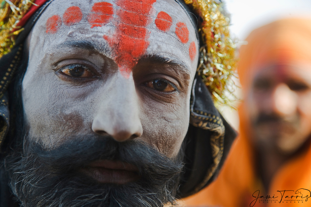 Close up portrait of a man staring into the camera with a decorated face painted for the camel fair,,Pushkar camel fair, Rajasthan, India