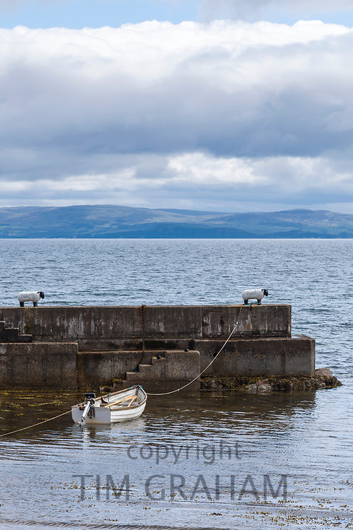 Rowing boat moored to a sheep shape bollard on the seawall in harbour near Corrie on the Isle of Arran, Scotland