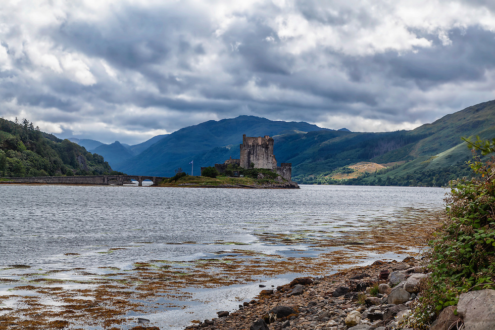 Eilean Donan offers one of the most iconic images of Scotland. It is situated on an island at the point where three great sea lochs meet, and surrounded by some majestic scenery.<br /> <br /> First inhabited around the 6th century, the first fortified castle was built in the mid 13th century and stood guard over the lands of Kintail. Since then, at least four different versions of the castle have been built and re-built as the feudal history of Scotland unfolded through the centuries.<br /> <br /> Partially destroyed in a Jacobite uprising in 1719, Eilean Donan lay in ruins for the best part of 200 years until Lieutenant Colonel John MacRae-Gilstrap bought the island in 1911 and proceeded to restore the castle to its former glory. After 20 years of toil and labour the castle was re-opened in 1932.<br /> <br /> This photograph is a colour version of the view of Eilean Donan Castle from the north, on Loch Alsh through to Loch Duich. The photograph can be purchased as print, mounted print in frames, canvas or aluminum or as a digital file.