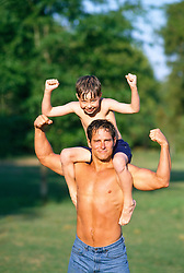 Good looking shirtless man with a boy on his shoulders;both making a muscle pose