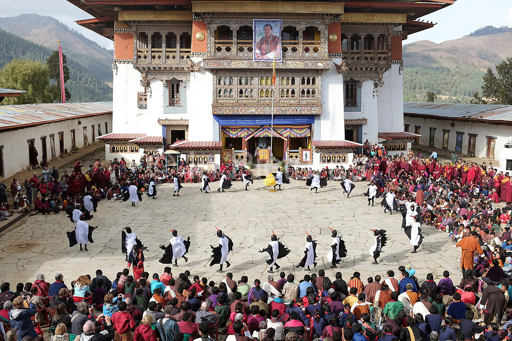 "Children from Bayta primary school dance the Black-necked Crane dance ""Ngachey Thrung Thrung Detshu"" at Gangte Goemba, Phobjikha Valley, Bhutan. Every year on November 11th, the local community hosts the Black-necked Crane festival at Gangtey Goenpa, to highlight its significance to the valley. Phobjikha Valley is the most significant overwintering ground of the rare and endangered Black-necked Crane in Bhutan."