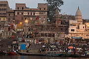 Pilgrims visiting the Holy city and colourful rowing boats on the Ganges river at Varanasi, Uttar Pradesh, India