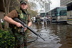 01 Sept, 2005. New Orleans, Louisiana.<br /> Mass evacuation begins. An armed National Guardsman maintains order over exhausted former residents of the Superdome 'shelter of last resort' as they wade through flood water to get to the first busses evacuating people from New Orleans to destinations unknown.<br /> Photo©; Charlie Varley/varleypix.com